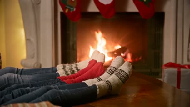 Family with child in knitted woolen socks warming at burning fireplace at house