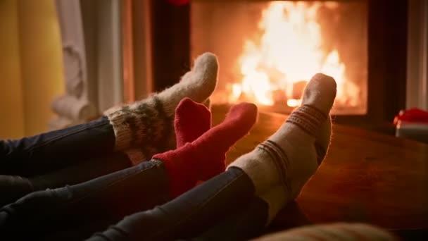 Closeup rodiny ve vlněných ponožek oteplování hořícího krbu v domě
