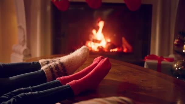 Closeup mužských a ženských nohou ve vlněných ponožek oteplování na krb