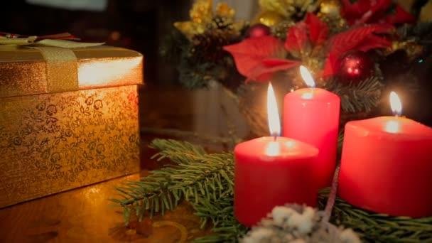 Detailní záběr dolly tří hořící svíčky a vánoční dárky v obývacím pokoji