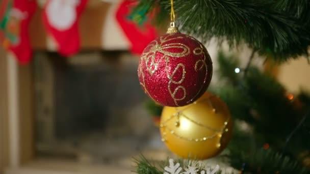 Detailní záběr na krásné červené cetka visí a předení na vánoční strom vedle zdobené krb