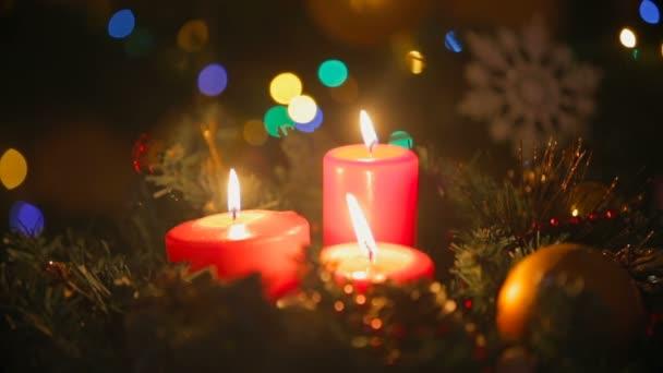 Closeup vánoční věnec s třemi hořící červené svíčky. Rozmazané zářící barevná světla na pozadí