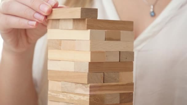 Closeup of businesswoman putting blocks and bricks of high tower. Concept of stability, development, success and business growth. Building and developing business