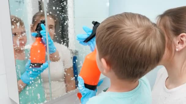 Kleiner Kleinkind Junge Anwendung chemischer Reinigungsmittel aus Spray beim Waschen Badezimmerspiegel mit Mutter. Kinder und Erwachsene bei Hausarbeit und Aufräumarbeiten zu Hause