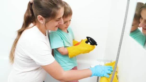 Kisgyerek, anya mossa és tisztítja a csapot a fürdőszobában. Boldog mosolygó család háztakarítást és házimunkát végez