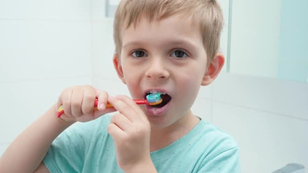 Funny toddler boy smiling and laughing while brushing and clening teeth with toothbrush in bathroom