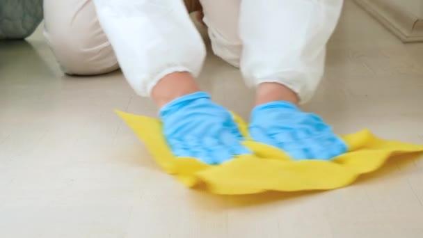 Detailní záběr hospodyně nebo hospodyně v lékařských rukavicích dezinfekci a čištění podlahy doma s chemickým čisticím prostředkem nebo čisticím prostředkem.