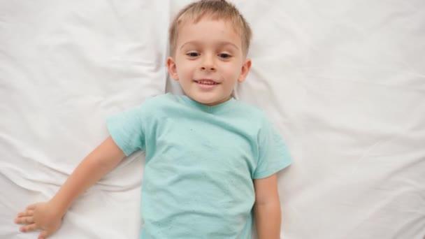 Portrét usměvavého chlapečka v pyžamu ležícího na velké posteli s bílými prostěradly a dívajícího se do kamery. Koncept šťastných dětí, které se dobře baví doma
