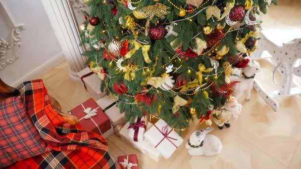 Horní pohled na spoustu dárkových krabic pod zdobené vánoční stromeček v obývacím pokoji v krásném domě. Zimní dovolená pozadí nebo pozadí.