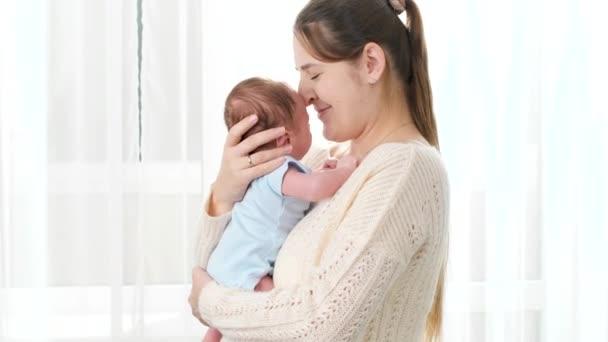 Portrét šťastné usměvavé matky mazlící se a dívající se na svého novorozeného syna proti velkému oknu v domě. Koncept rodinného štěstí a milujících rodičů s malými dětmi.