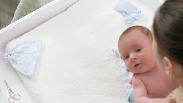 Zpomalený pohyb mladé matky, jak dává malého synka na měkkou přikrývku na přebalovací stůl. Koncepce novorozenců, hygiena a zdravotní péče. Pečující rodiče s malými dětmi.