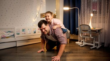 Cheerful little boy riding piggy back on his father at night. Concept of child playing with parents and family having time together at night