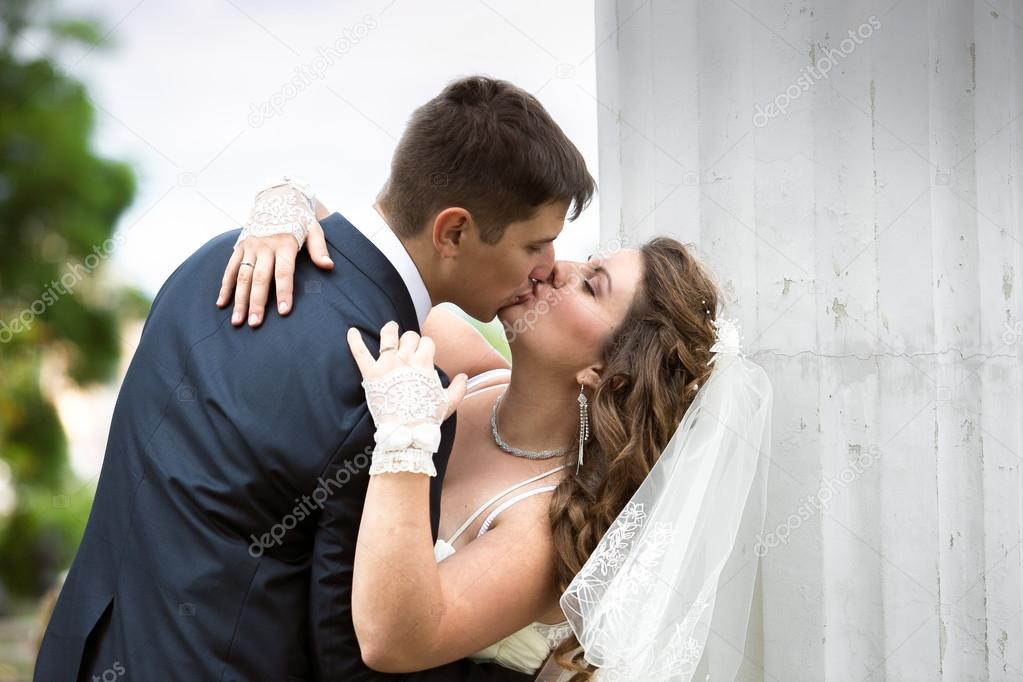 beautiful bride and groom kissing passionately on street