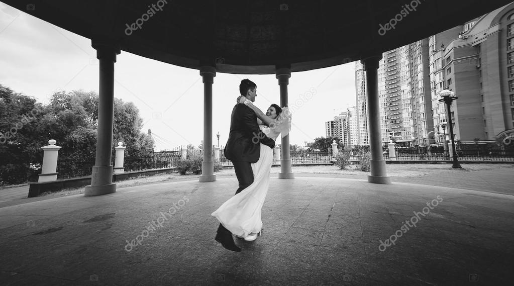 Monochrome shot of bride and groom dancing at alcove in park