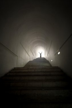 person standing in the end of tunnel at light beam with hands ra