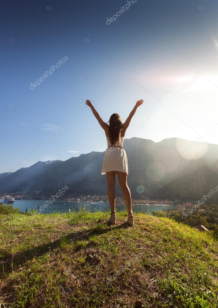 woman standing on top of hill against bright sun with outstretch