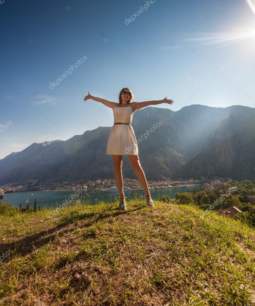 woman standing on top of mountain and stretching out hands