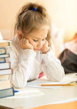 Portrait of upset schoolgirl looking at textbook with homework