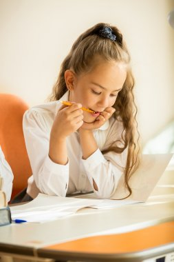 portrait of schoolgirl chewing pencil while doing homework