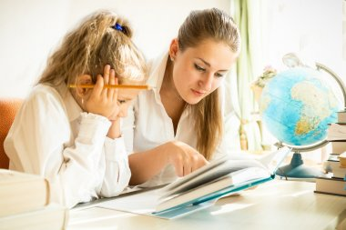 mother and daughter reading textbook while doing homework