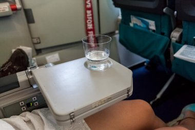 glass of water standing on table in aircraft