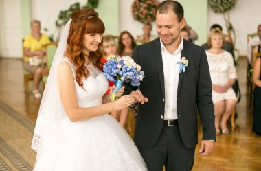 portrait of smiling bride and groom changing with wedding rings