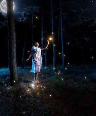 young woman at night forest with full moon jumping high to reach