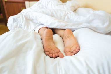 Photo on bed of girls feet lying on pillow