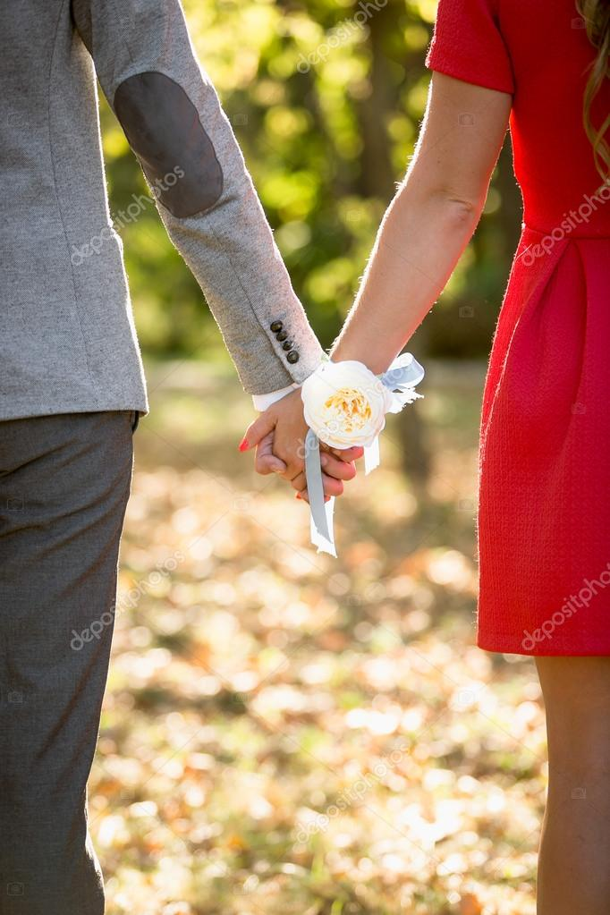Happy couple holding hands at park