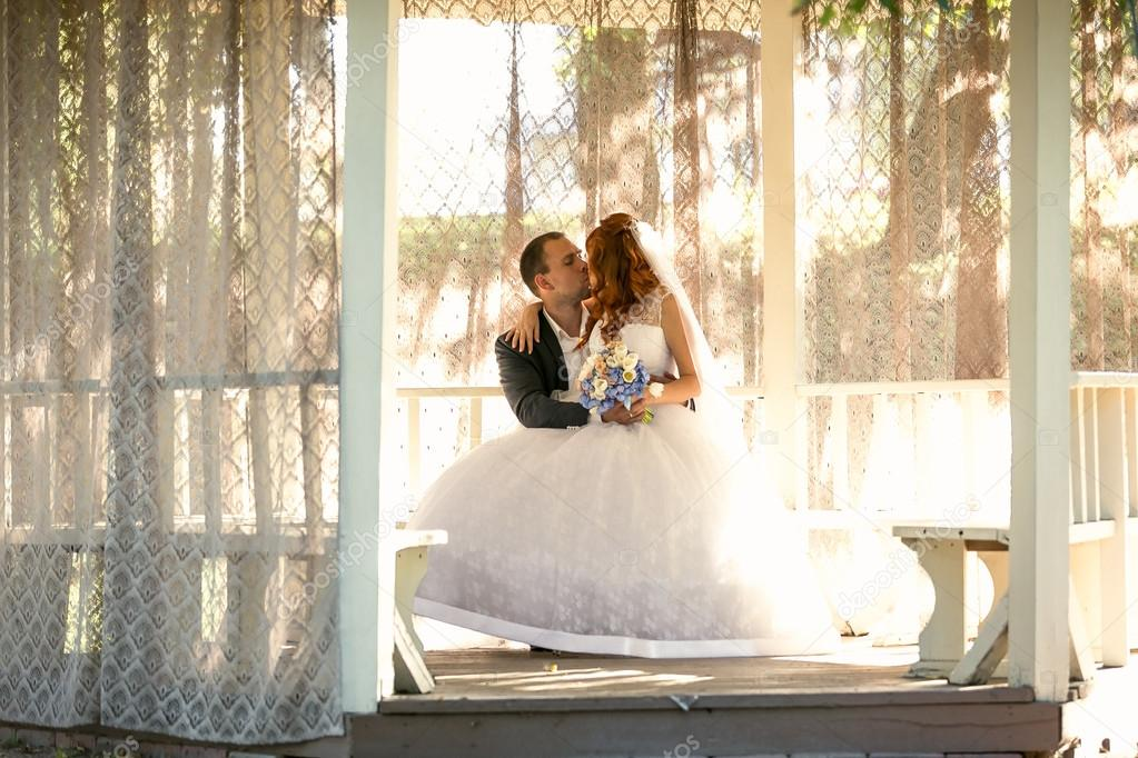 bride sitting on grooms legs on bench at gazebo