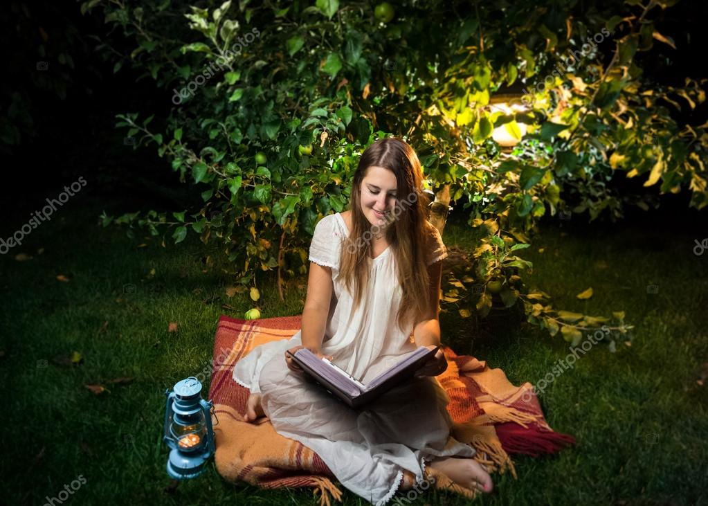 smiling woman sitting at night in garden and reading big old boo