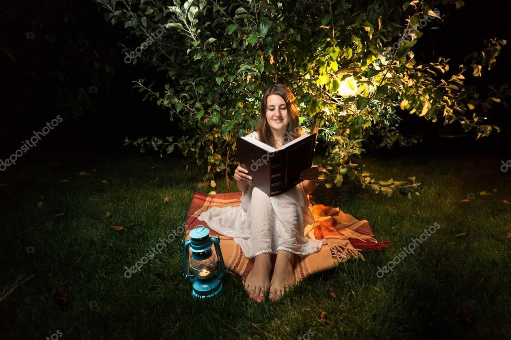 smiling woman sitting on grass at night and reading big old book