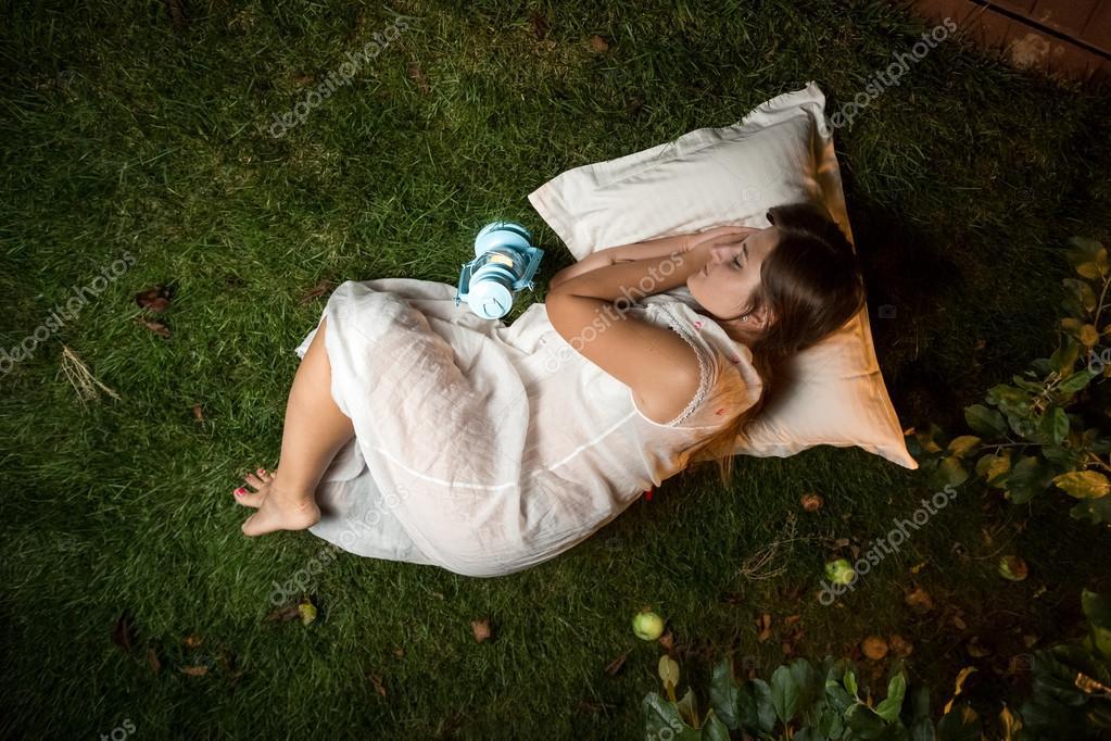 Beautiful brunette woman sleeping at night garden on pillow foto de kryzhov
