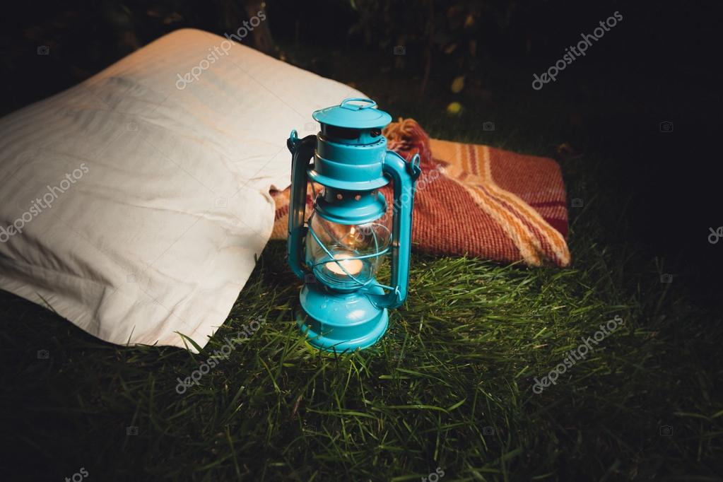 old lantern, pillow and blanket lying on grass at night