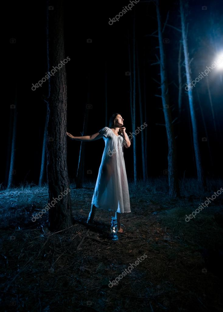 woman in white nightgown looking at beam of light at night fores