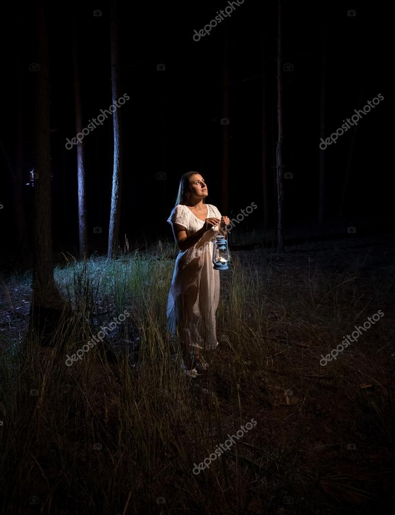 woman with gas lamp  standing in scary dark forest