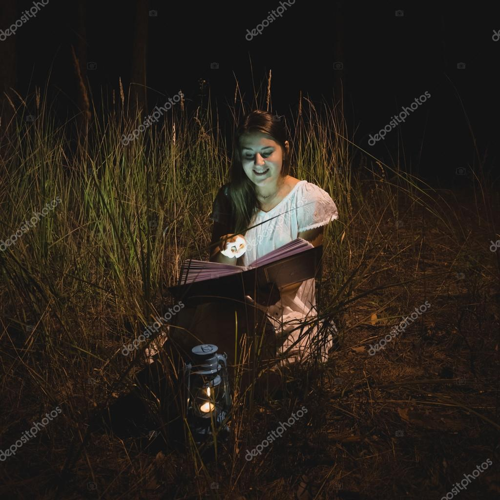 smiling woman reading magical book at night forest
