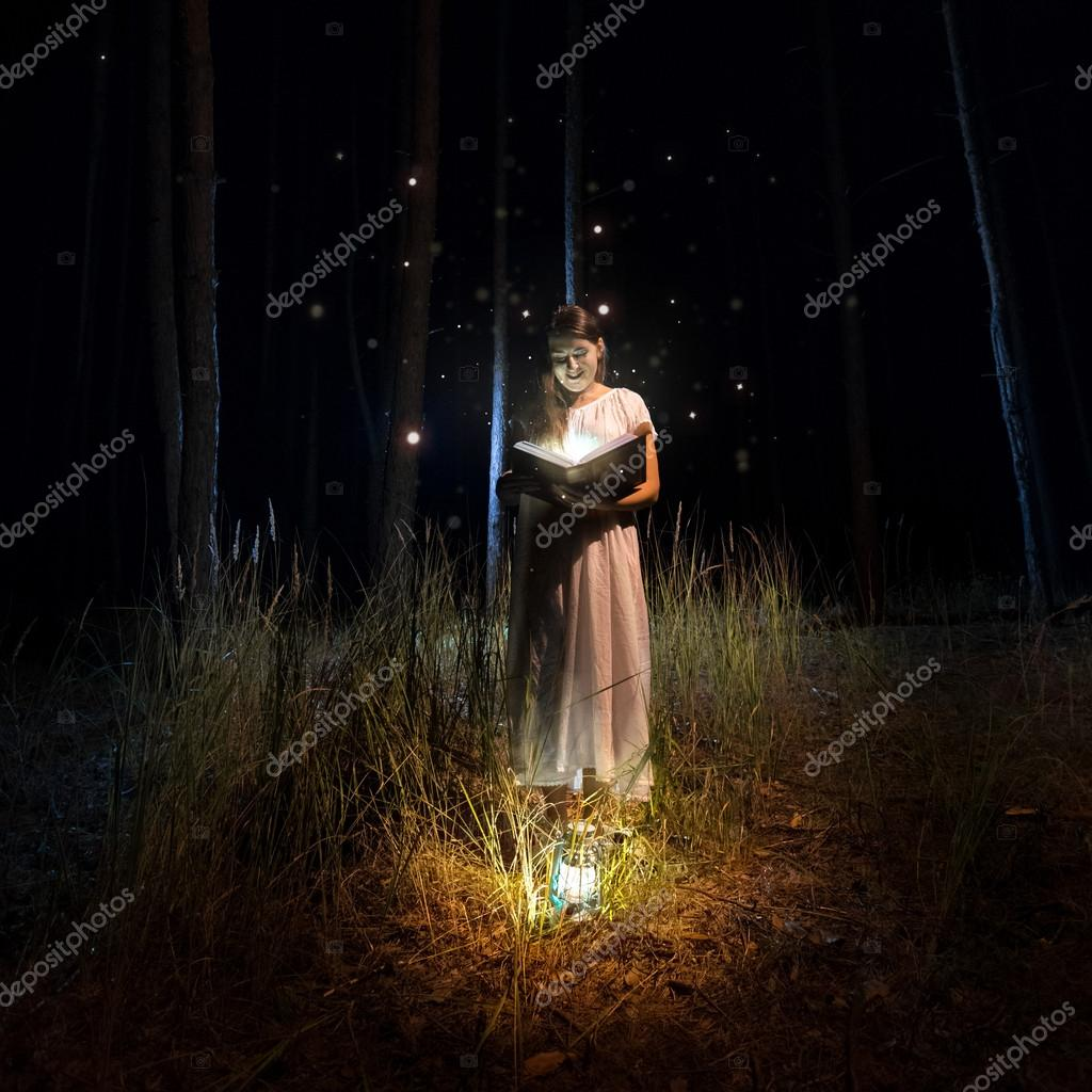 woman in long dress reading big old book at mysterious forest wi