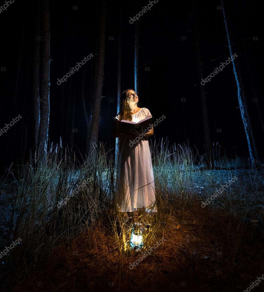 Mysterious shot of woman reading big book at dark forest