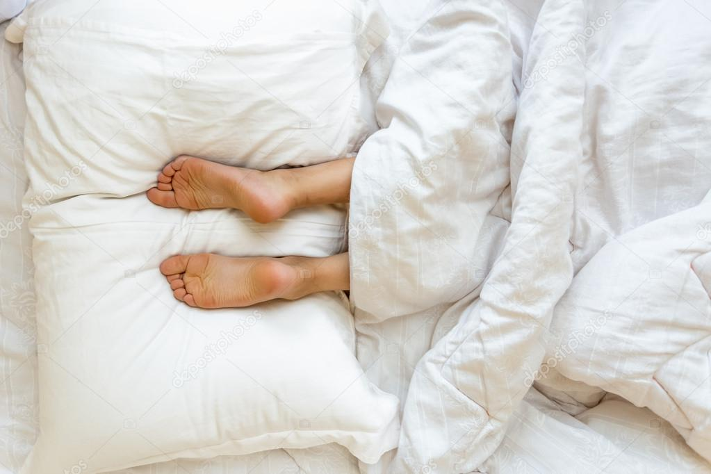 Feet lying on soft white pillow at bed
