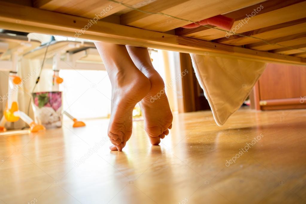 Closeup shot of female feet under bed