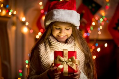 Little girl looking at open box with Christmas present