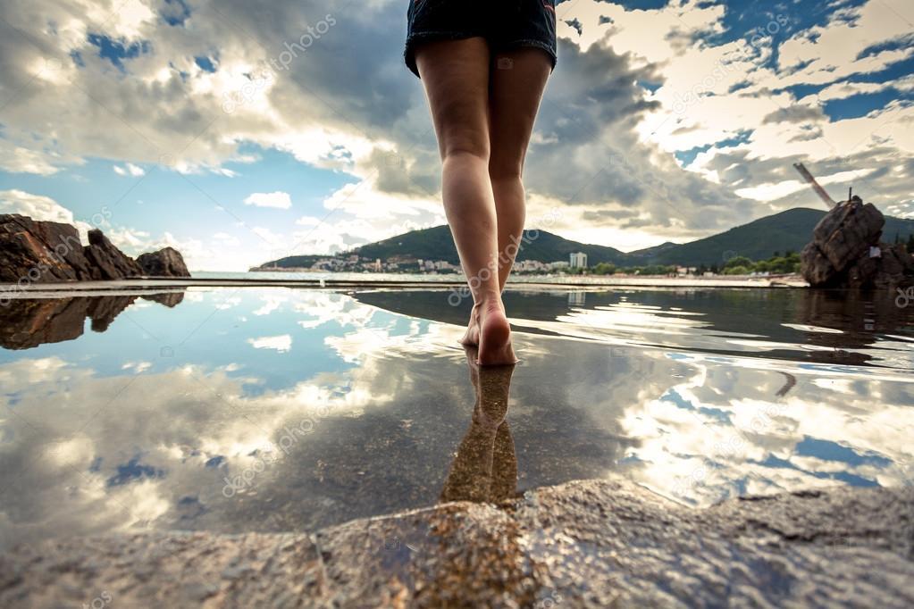 Rear view photo of beautiful female legs walking on water surfac