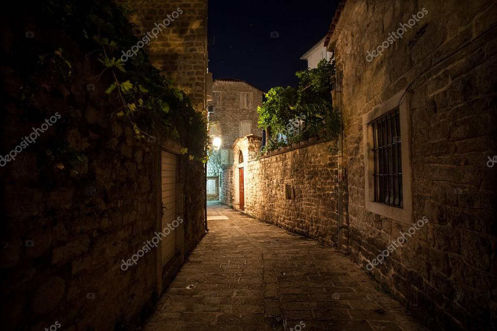 old narrow street lit by gas lanterns at night
