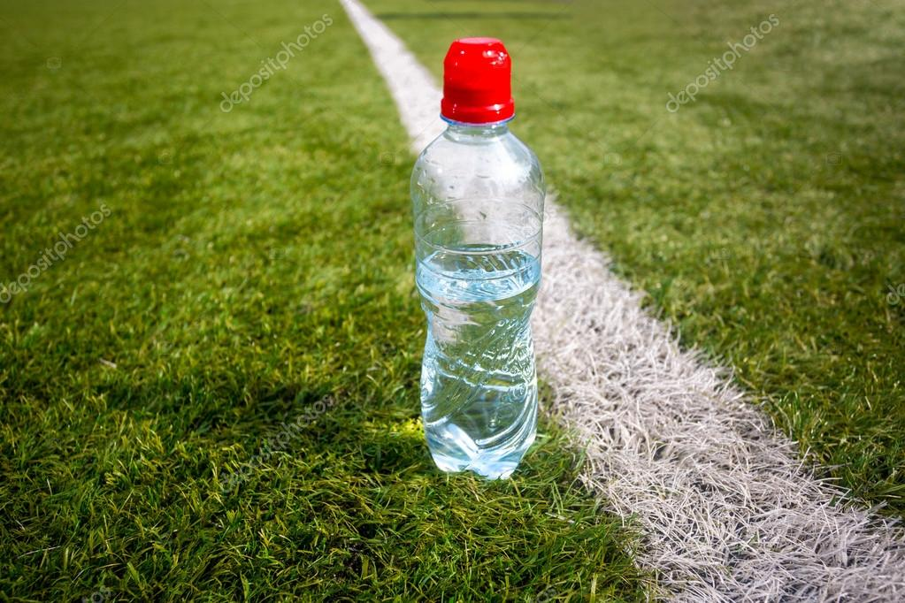 plastic bottle of water on green grass at football field