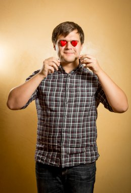 funny man holding red hearts in front of eyes