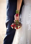 bride hugging groom and holding wedding bouquet