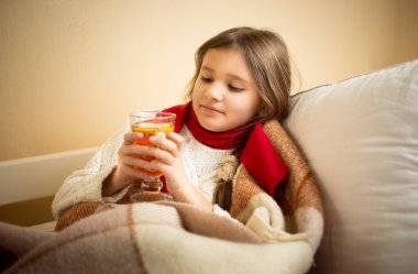 Cute girl got flu and holding cup of tea at bed