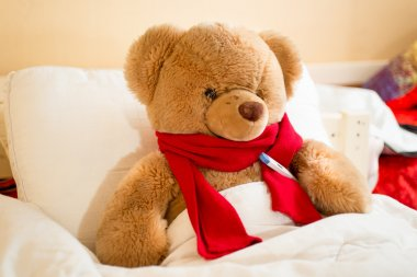 brown teddy bear in read scarf lying in bed with thermometer