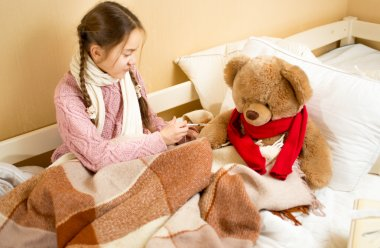 girl sitting on bed and doing injection to brown teddy bear